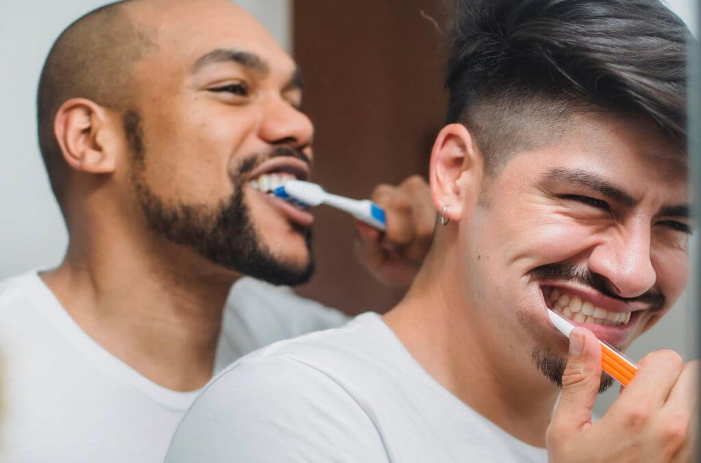 men brushing their teeth using artificial sweeteners